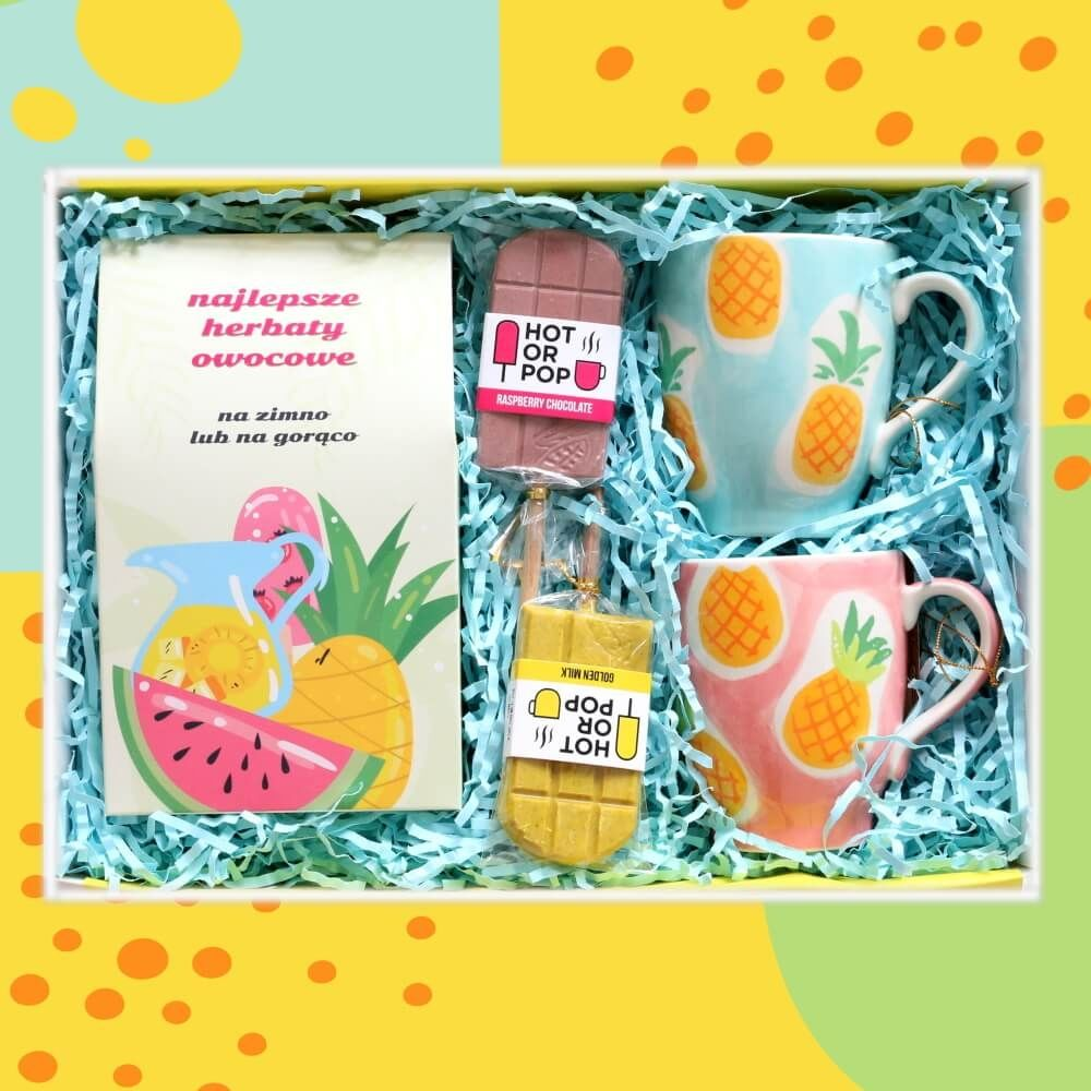 Zestaw prezentowy na wyjątkową okazję TeaBox NAJLEPSZE OWOCOWE. Zestaw 10 herbat owocowych o różnych smakach 10x 5/8g z zaparzaczem, dwa ananasowe kubki i dwa kolorowe lizaki czekoladowe